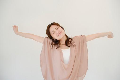 日本人 女性 女 30代 アラサー グレーバック 背景 グレー ポーズ ハーフアップ 髪型 茶髪 ナチュラル 私服 カジュアル ピンク ピンクベージュ 伸び 背伸び ストレッチ 解放 解放感 表情 スッキリ すっきり 両腕 腕 伸ばす mdjf013
