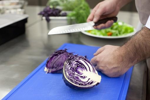 厨房 台所 キッチン 料理 調理  コック シェフ 料理人 包丁 ナイフ 切る カット まな板 レストラン 仕込み 下準備 野菜 青 バット ボディパーツ 腕 持つ 手 紫キャベツ レッドキャベツ 赤きゃべつ 真っ二つ 男性 外国人