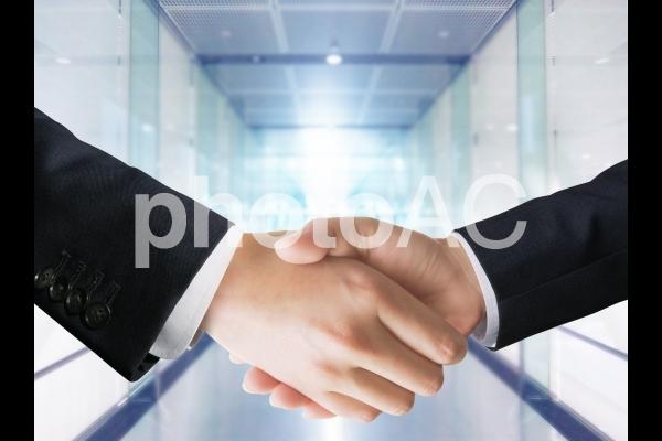 ビジネスマンの契約成立の握手とオフィス背景の写真