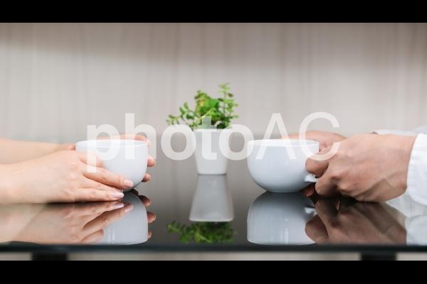 コーヒーを飲みながら会話する男女の写真
