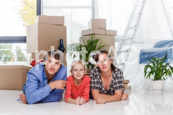 引越しの段ボールの前で寝転ぶ家族1の写真