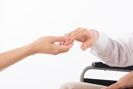 老人 高齢者 お年寄り シニア 手 両手 介護士 看護師 エプロン 支える 添える  介護 不自由 椅子 ヘルパー 白バック 白背景 車いす 車椅子 白 シャツ 座る ベージュ 茶色 握る アップ