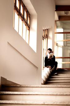 本 ブック 書物 書籍 図書 読書 読む 趣味 勉強 人物 男性 男 外国人 若い 若者 髭 20代 全身 ページ 捲る めくる 開く 座る クッション 窓際 窓辺 眺める 段々 段差 階段 mdfm079