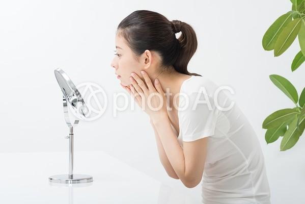 鏡で肌をチェックする女性(横顔)4の写真