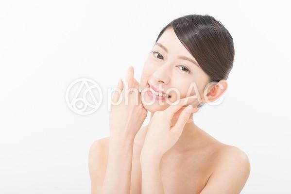 両手を頬によせポーズをとる女性3の写真