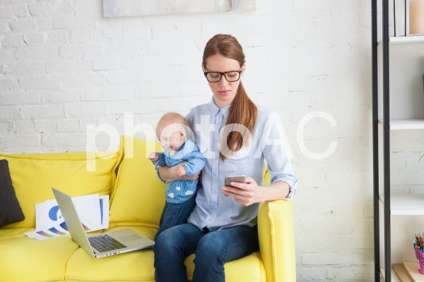 自宅で赤ちゃんを抱っこしながら仕事するお母さん6の写真