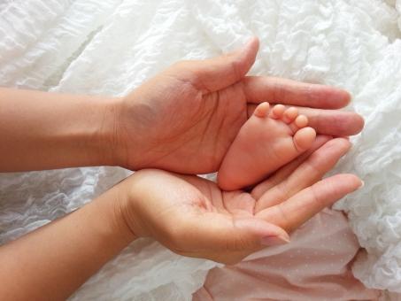 赤ちゃんの足と母親の手の写真