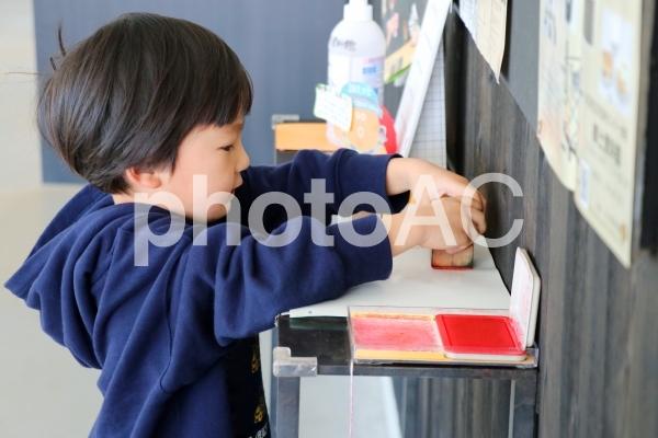 スタンプラリーでスタンプを押す子供の写真