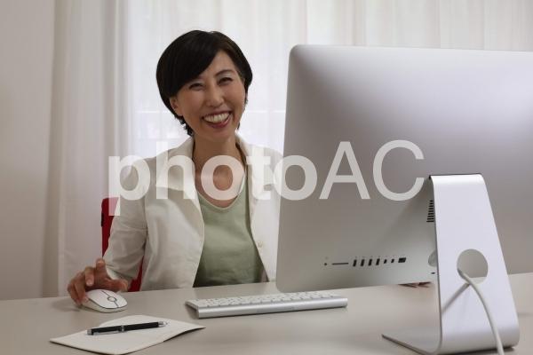 パソコンの前で笑顔の女性の写真