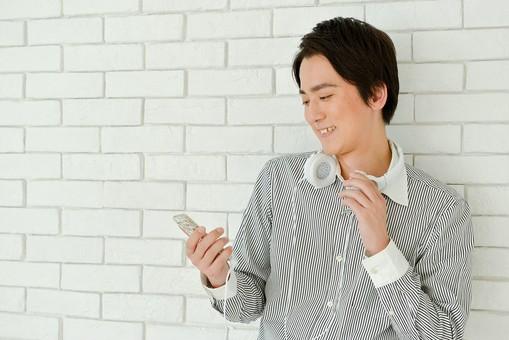日本人 男性 男 20代 若い ファッション カジュアル インフォーマル 仕事 オフィス 会社 クリエイター デザイナー グラフィックデザイナー webデザイナー シャツ ストライプ 携帯電話 携帯電話を見ている 営業 爽やか 爽快 笑顔 にこやか イヤホン イヤフォン ヘッドホン ヘッドフォン スマホ スマートフォン mdjm024