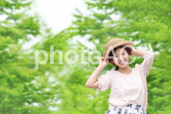 森林と帽子をかぶった笑顔の女性の写真