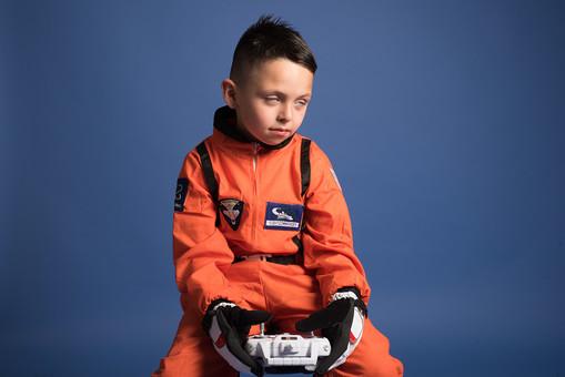 背景 ダーク ネイビー 紺 男の子 男子 男児 男 子ども こども 子供 1人 ひとり 一人 児童 宇宙服 宇宙 服 スペース スペースシャトル 宇宙飛行士 飛行士 オレンジ 希望 夢 将来 未来 体験 職業体験 職業 小道具 小物 おもちゃ コントローラー リモコン コントロール 座る 腰かける 白目 脱力  外国人 mdmk009