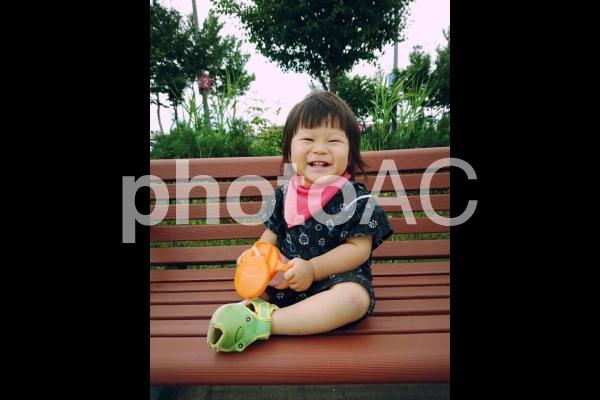 公園のベンチで休憩する子供の写真