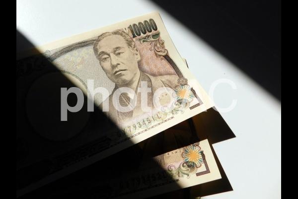 1万円札と光と影の写真