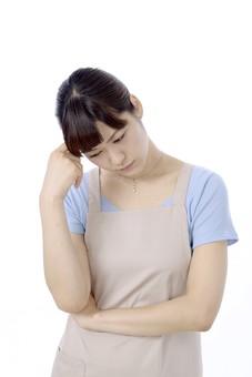 人物 屋内 白バック 白背景 日本人 1人 女性 20代 30代 エプロン  奥さん 奥様 婦人 家庭人 夫人 主婦 若い ポーズ 表情 手 頭 当てる 手を頭に当てる  考える 考えごと 心配 心配事 心配する 不安 悩み 悩む 思考 思索 うつむく 頭痛 痛い 痛み 痛む 不調  横向き 辛い mdjf018