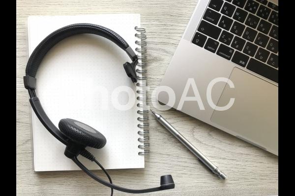 ノートパソコンとヘッドセットとノートとペン(木目背景)、リモートワーク・テレワークイメージの写真