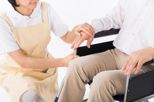 老人 高齢者 お年寄り シニア 女性 おんな 女  2人 二人 手 両手 介護士 看護師 エプロン 支える 添える  介護 不自由 椅子 ヘルパー 白バック 白背景 車いす 車椅子 白 シャツ 座る ベージュ 茶色 握る