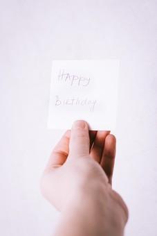 バースデーカード 誕生日 お祝い 文字 英語 メッセージ 伝言 ハッピーバースデー ギフト 贈り物 渡す 手渡し プレゼント 屋内 人 人物 手 持つ 白 白バック 白背景 1個 横から視線 思いやり 真心 Happy Birthday