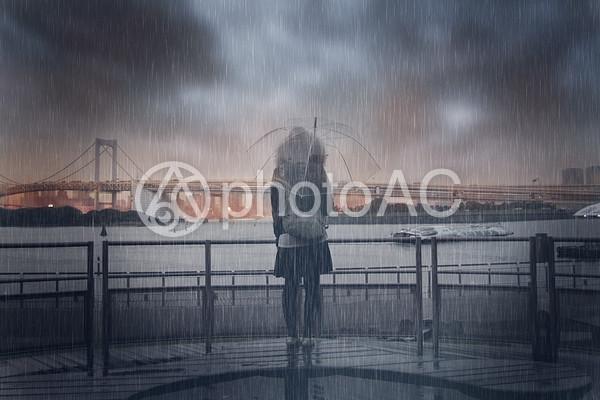 雨の中海の前に佇む女性の写真