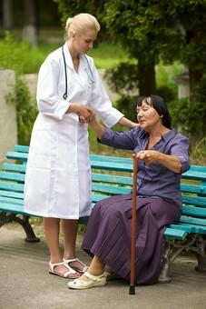 屋外 野外 外 病院 庭 公園 ベンチ 外国人 老人 高齢者 女性 おばあさん おばあちゃん 患者 女医 白人 金髪 白衣 医師 医者 スカート 座る 杖 つえ 突く つく 持つ 立つ 立ち上がる 手伝う 手助け 介護 介助 手を引く 立ち上がらせる mdfs016 mdff142