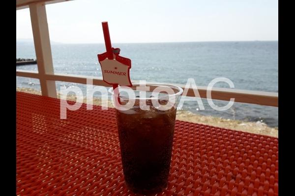 ビーチのカフェで冷たいコーラを飲むの写真