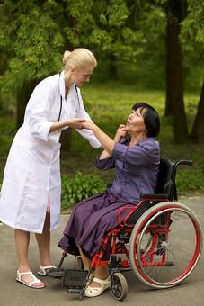 屋外 野外 外 病院 庭 公園 外国人 老人 高齢者 女性 おばあさん おばあちゃん 患者 女医 白人 金髪 白衣 医師 医者 スカート 車椅子 車いす 乗る 座る 散歩 歩く 立ち止まる 止まる 立つ 立たせる 立ち上がる 立ち上がらせる 手を持つ 手を引く 助ける 介助 介護 手伝う 手をとる mdfs016 mdff142