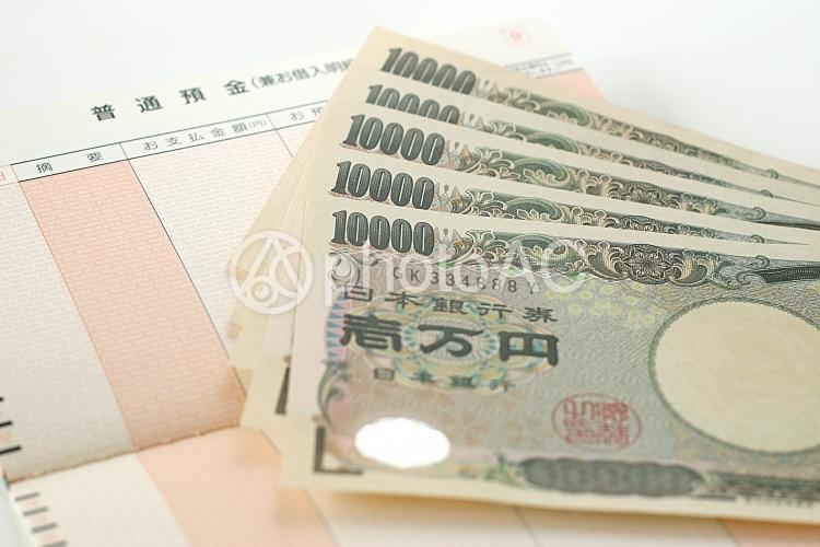 通帳と一万円札の写真