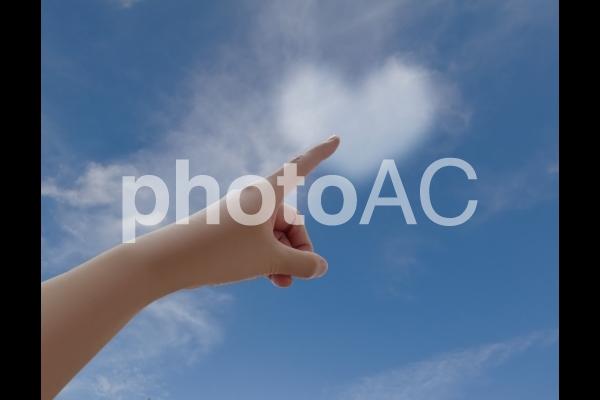 空のハートの形の雲を指差すの写真