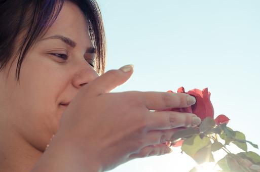 外国 海外 屋外 野外 自然 人物 1人 外国人 白人 セルビア人 大人 若い 女性 女 女の子 顔 ブルネット 黒髪 セミロング まとめ髪 ひっつめ髪 無造作ヘア 空 陽射 逆光 植物 造花 薔薇 バラ ばら 花 赤 葉 微笑み 微笑 笑顔 香り 嗅ぐ 匂う 香る アップ mdff021