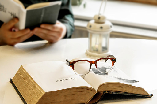 本 ブック 書物 書籍 図書 読書 読む 趣味 勉強 ページ 捲る めくる 開く 接写 クローズアップ 眼鏡 めがね メガネ フレーム おしゃれ 置く 乗せる 休憩 休息 休む 一息 人物 ランプ 机 テーブル