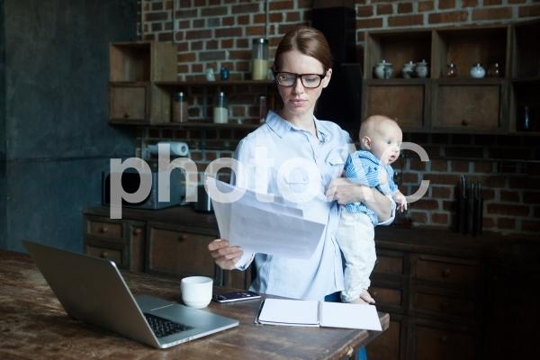 自宅で赤ちゃんを抱っこしながら仕事するお母さん11の写真