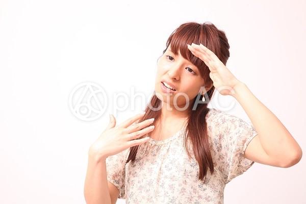 汗を拭いながら片手で扇ぐ女性の写真