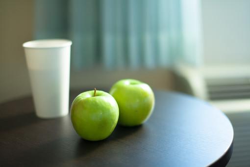 りんご リンゴ フルーツ 果実 植物 青リンゴ 緑 黄緑 甘い 酸っぱい 美味しい デザート 紙コップ 飲み物 飲む 食べる 生物 食材 食べ物 成熟 テーブル 机 置く カーテン 室内 屋内 ぼやける ピンボケ 景観 無人 アメリカ 外国