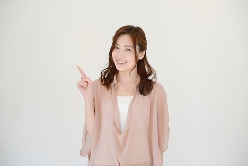 日本人 笑顔 スマイル 女 女性 ポーズ カジュアル 私服 ナチュラル サイン 30代 ピンク グレー 指 茶髪 人差し指 ポイント 指さす アジア人 指す 重要 ピンクベージュ 髪型 グレーバック ハーフアップ mdjf013 アラサー コツ