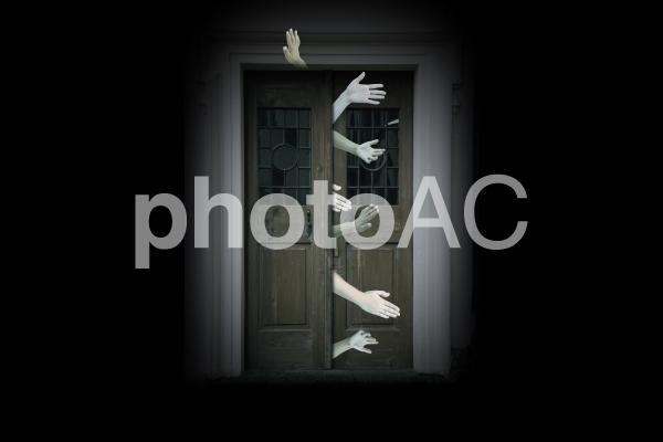 観音開きのドアから伸びる血色のない無数の手首の写真