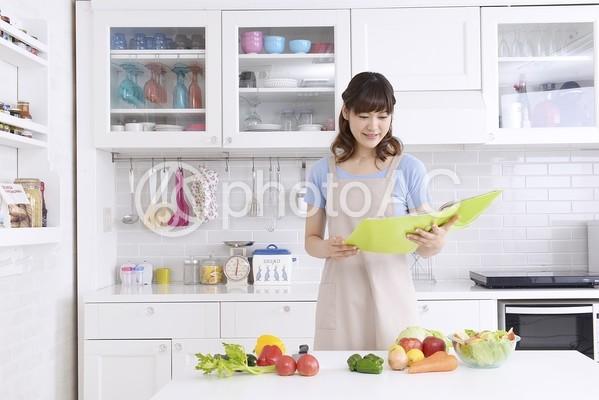 キッチンでレシピを見る女性1の写真