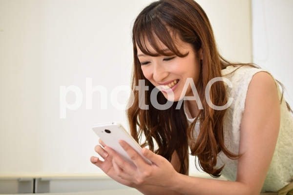 スマホを見て笑う女性の写真