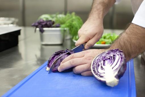 厨房 台所 キッチン 料理 調理  コック シェフ 料理人 包丁 ナイフ 切る カット まな板 レストラン 仕込み 下準備 野菜 青 バット ボディパーツ 腕 持つ 手 紫キャベツ レッドキャベツ 赤きゃべつ ざっくり  男性 外国人