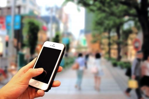 スマホ片手に街歩きの写真