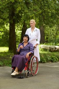 屋外 野外 外 病院 庭 公園 外国人 老人 高齢者 女性 おばあさん おばあちゃん 患者 女医 白人 金髪 白衣 医師 医者 スカート 車椅子 車いす 乗る 座る 押す 散歩 歩く 立ち止まる 止まる 全身 mdfs016 mdff142