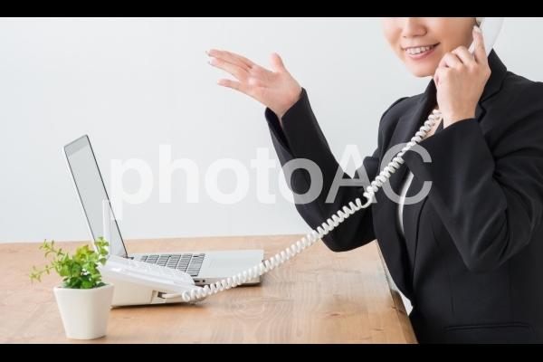 電話と笑顔のビジネスウーマンの写真