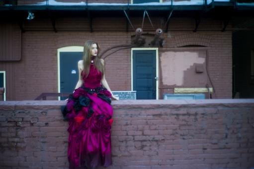 人間 人物 ポートレート ポートレイト 女性 ロングヘア 外国人 外国の女性 外国人女性 ブロンド 金髪  赤いドレス 赤ドレス バラドレス 貴婦人 ゴシック アメリカンスリーブ 肩出し  ネックレス アクセサリー 首飾り レンガ ブロック 塀 座る 腰かける 腰を下ろす ドア セクシー 色気 mdff098