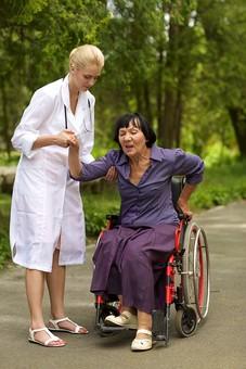 屋外 野外 外 病院 庭 公園 外国人 老人 高齢者 女性 おばあさん おばあちゃん 患者 女医 白人 金髪 白衣 医師 医者 スカート 車椅子 車いす 乗る 座る 散歩 歩く 立ち止まる 止まる 立つ 立たせる 立ち上がる 立ち上がらせる 手を持つ 手を引く 助ける 介助 介護 手伝う mdfs016 mdff142