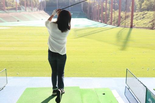 ゴルフの練習場で練習をする初心者女性の写真
