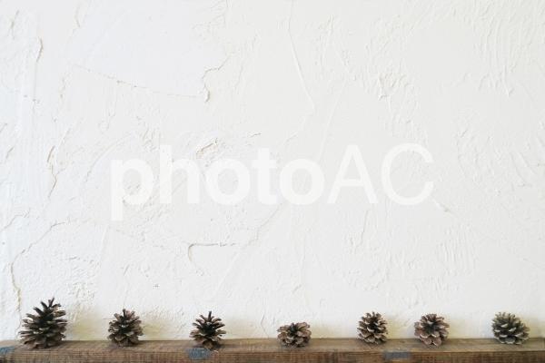 白壁と木目フレームと松ぼっくりの写真