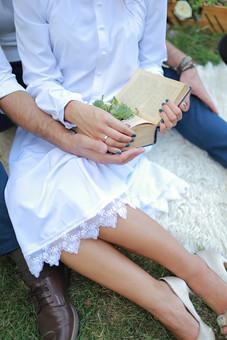 屋外 ガーデンウェディング 男女 男 女 下半身 足もと 足元 白 ドレス ワンピース 読書 植物 緑 デート 重ねた手 レース 毛皮 ブレスレット 指輪 婚約指輪 結婚指輪 本 マニキュア 寄り添う二人 カップル