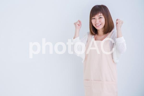 ガッツポーズするエプロン姿の女性の写真
