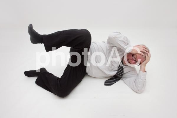 頭痛で頭を抱える男性の写真