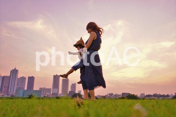 草原で遊ぶ親子の写真