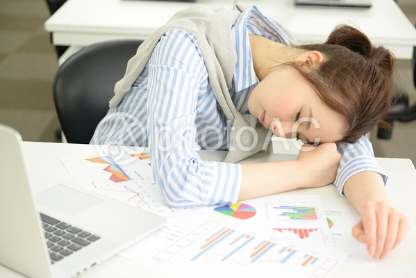 机に突っ伏して寝るキャリアウーマン3の写真